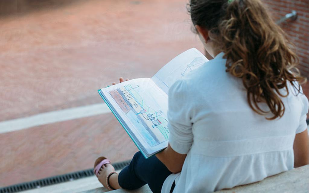 Noia llegint al pati